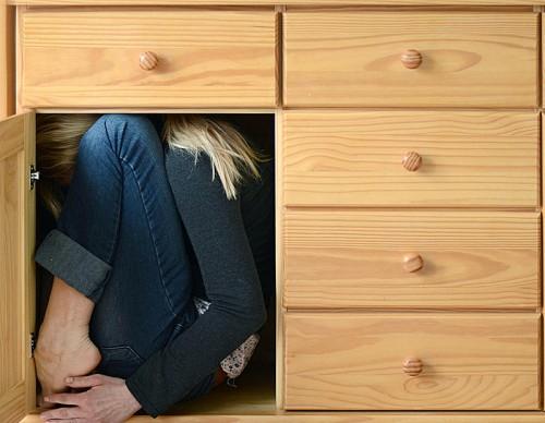 Eine Frau, eng zusammengekauert einer Kommode